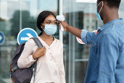 Airport Worker Checking Black Female Passenger's Temperature With Electronic Thermometer After