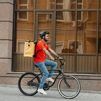 Fast delivery in city. Young man with helmet and delivery backpack rides bicycle