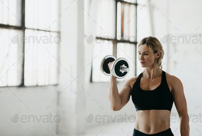 Strength training in studio. Athletic woman in sport bra engaged with dumbbells