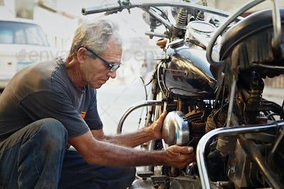 Senior Man Fixing Vintage Motorcycle Engine