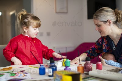 Young girl using paints at kitchen table with mother sitting nearby holding baby