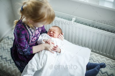 Young girl sitting holding newborn baby