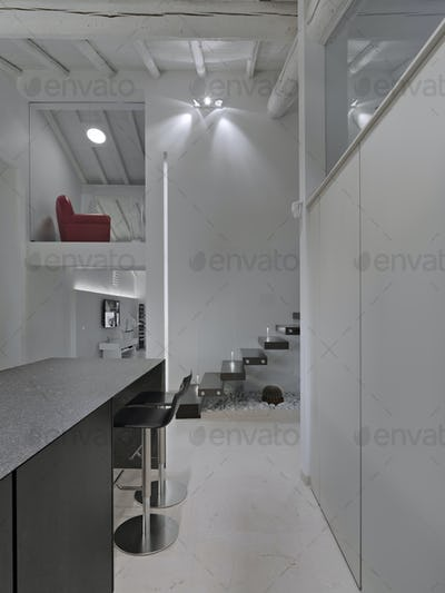 Modern Kitchen Interior on the Background there is a Staircase