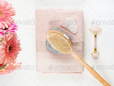 Massage brush, stone, face roller on pink towel
