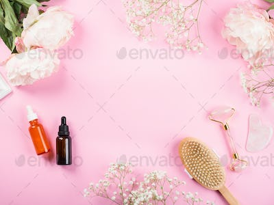 Pink beauty floral frame background with bottles