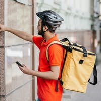 Modern food delivery. Young man with beard, with backpack and smartphone, ringing the bell