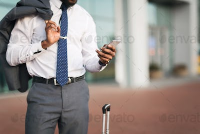Unrecognizable African Businessman Using Phone At Rail Station, Cropped