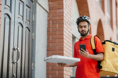 Pizza delivery. Serious delivery man with helmet, with backpack holding box and looking at