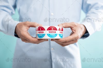 Unrecognizable man holding roll with stickers for voters