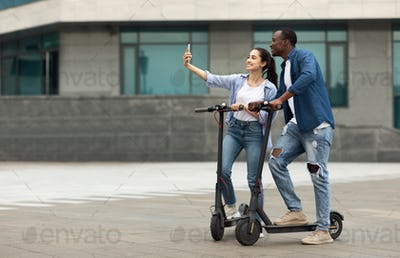 Friends having ride on motorized kick scooters, taking selfies