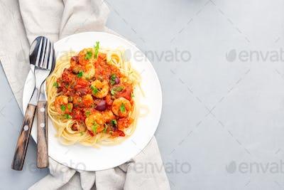 Shrimp linguine Puttanesca pasta with shrimps in tomato basil sauce, horizontal, top view