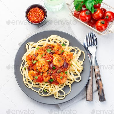 Puttanesca pasta with shrimps in spicy sauce, square, closeup