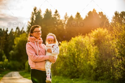 Mother and child walking on countryside road between agricultural fields towards vilage from forest