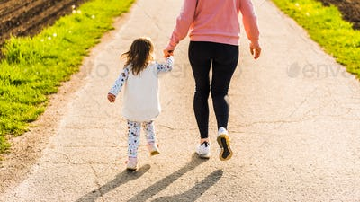 Mother and child walking on countryside road between agricultural fields towards forest in Austrian