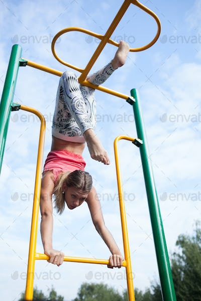 Beautiful young gymnast working out outdoors