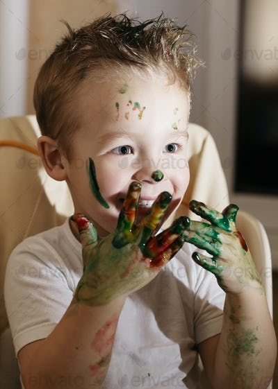 Excited little boy playing with finger paints