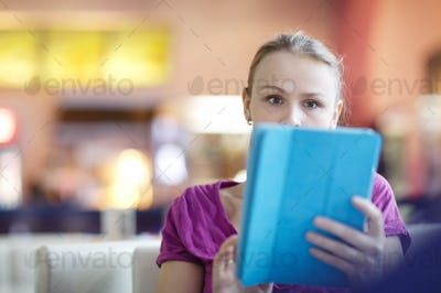 Woman in a terminal using her tablet