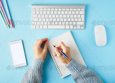 Faceless woman writing in notepad. Mobile phone with blank white screen display