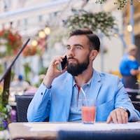 Stylish bearded male in a blue jacket using smartphone.