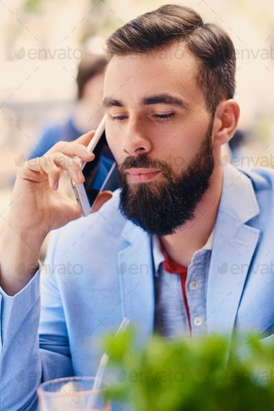 Stylish bearded male in a blue jacket using smartphone.