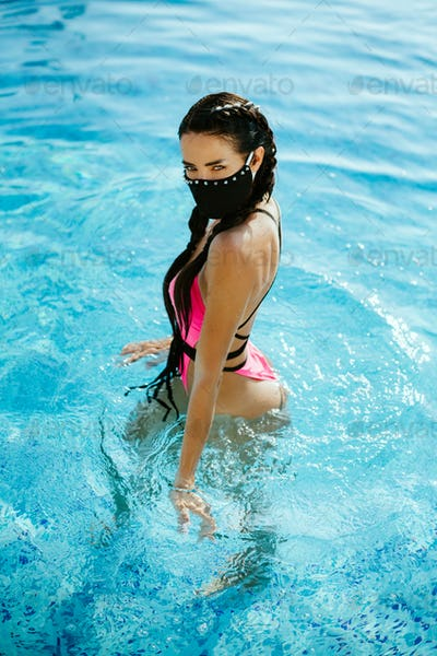 woman relax in swimming pool wearing face mask self isolation concept