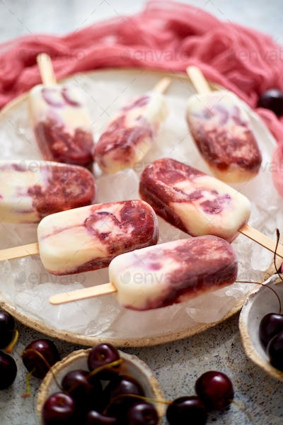 Fresh cream and cherry homemade popsicles placed on white ceramic plate with fruits and textile