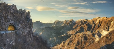 Alpi Apuane mountain road pass and tunnel view at sunset. Carrara, Tuscany, Italy.