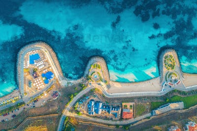 Aerial view of sandy beach, blue sea, restaurants at sunset