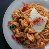 Spicy stir-fried pasta in white plate
