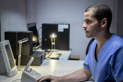 Health Care Male Worker In Hospital With Computer And Equipment