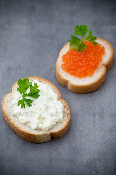 Bread with fresh cream cheese and red caviar on table.