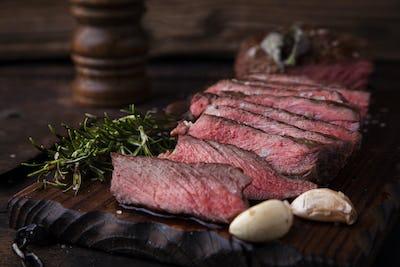 Sliced medium rare grilled beef steak with salt, rosemary and garlic