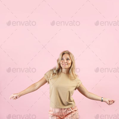 Caucasian blonde woman smiles and spreads her hands and looks up isolated on pink background