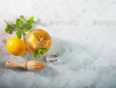 Lemon ice tea on concrete gray background with mint and ice, flat lay with copy space