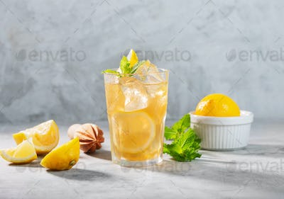 Glass of Lemon ice tea on concrete gray background with mint and ice