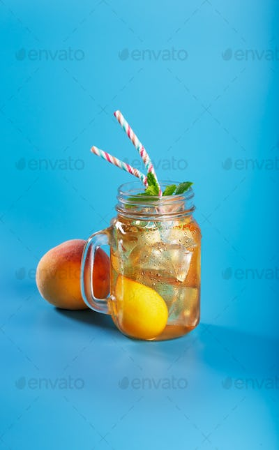 Peach ice tea drink on blue background with mint and ice