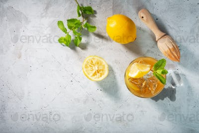 Lemon ice tea on concrete gray background with mint and ice, flat lay