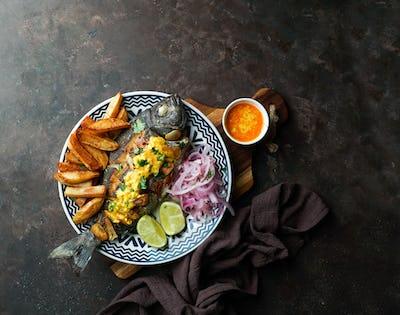 Chita frita al ajo, al ajillo, Peruvian food,  a whole fish, served wit rice