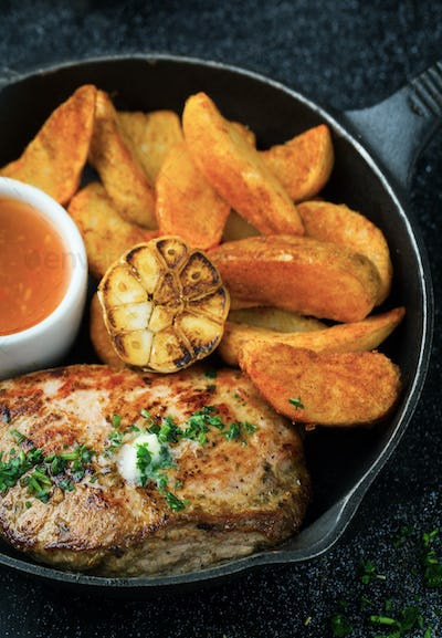 Delicious steak with baked potatoes, sauce and garlic