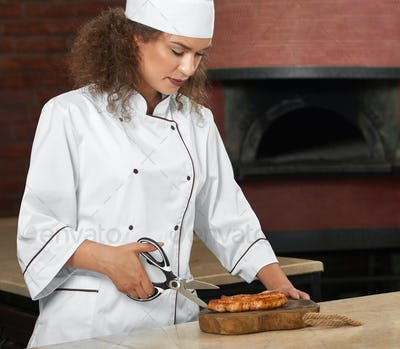Professional chef cutting chicken steak with scissors