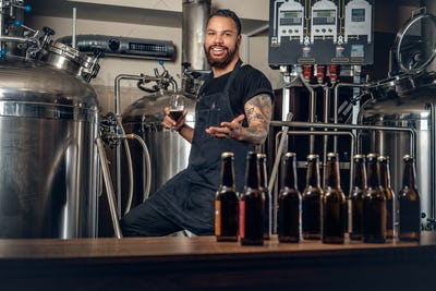 Black male manufacturer tasting beer in the microbrewery.