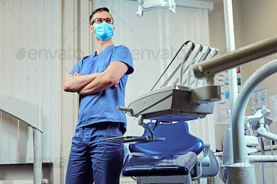 Dentist in a room with medical equipment on background.