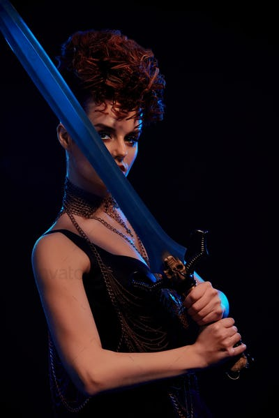 Dangerous warrior woman keeping big steel sword
