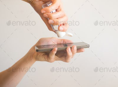 Female hand cleaning smartphone with sanitizer gel