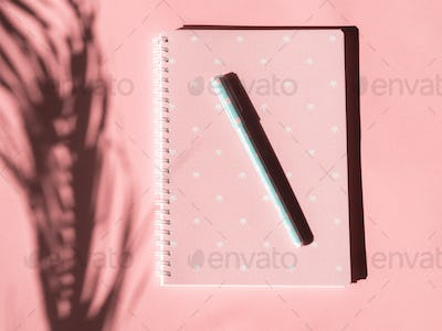 Pink notebook with pen and tropical plant shadow