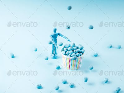 Human marionette and flying easter eggs on blue