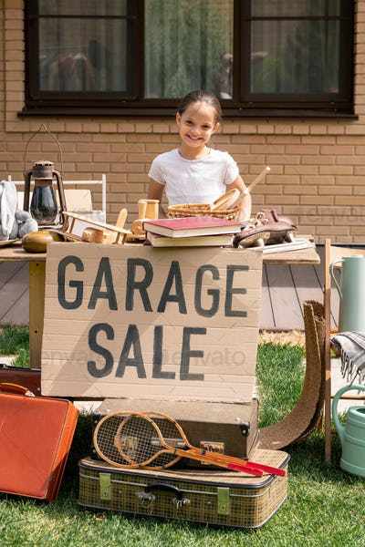 Smiling girl offering things at garage sale