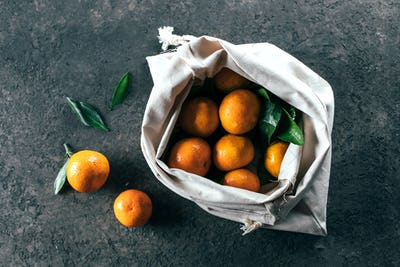 Ripe mandarine tangerine in cotton bag. Zero waste concept