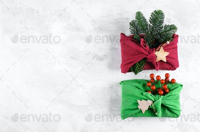 Holidal christmas concept. Furoshiki gifts present wrapping with linen fabric, fir tree branch