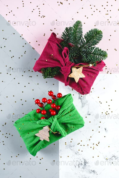 Holidal christmas concept. Furoshiki gifts present wrapping with linen fabric, fir tree branch
